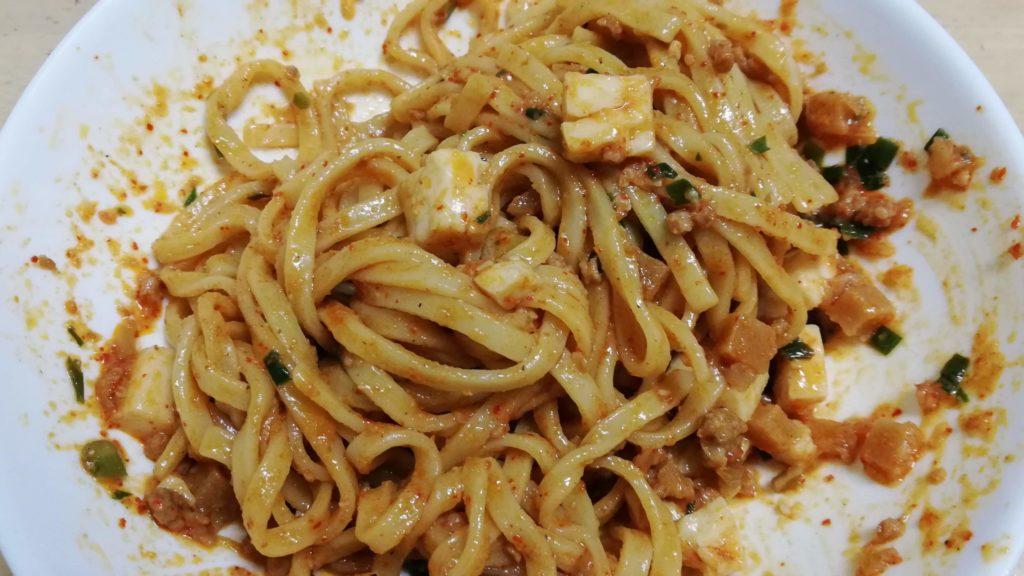 セブンイレブンの冷凍食品「蒙古タンメン中本 辛旨汁なし麻辛麺」の花椒入り辣油を半量投入後